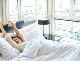 woman waking up in clean hotel bed