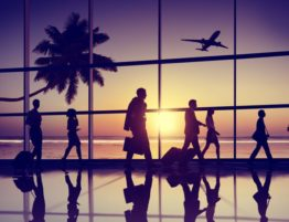 silhouette of travelers walking through airport